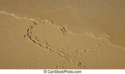 drawings in the sand. Sea wave washes a heart