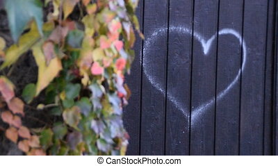 Drawn heart on the gate,next to the wall