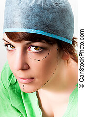 Drawn lines on a young woman face as marks for facial plastic surgery