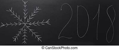 drawn snowflake with chalk on blackboard with year 2018.