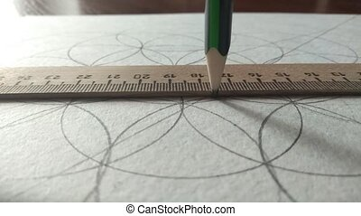draws a line with a pencil in a ruler, drawing with circles