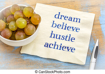 Dream, believe, hustle, achieve - text on napkin