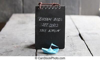 Dream big, set goals, take action on blackboard written