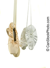 Small and big ballet toeshoes hanging; on white