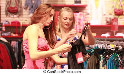 Cheerful female friends choosing a dress in a mall