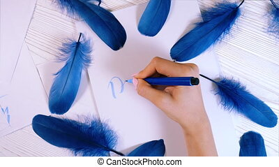 Dream. Female hand writes beautiful blue letters on canvas...