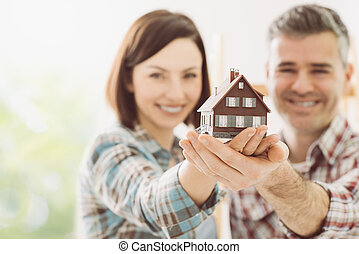 Dream house - Happy couple holding their dream house in...