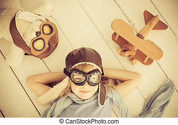 Dream - Happy child playing with toy airplane at home. Retro...