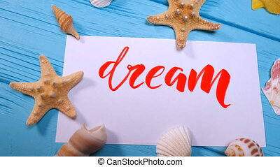 Dream text. Font of lettering motivational word on white canvas with red ink by calligrapher. Seashells and sea stars frame. Graphic design, handwriting, creation concept.
