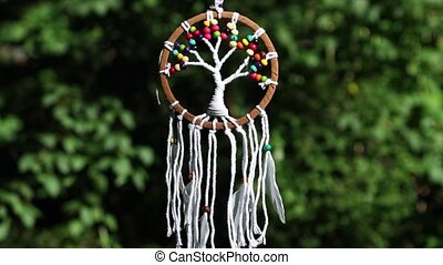 Dreamcatcher with feathers swaying with light wind against natural background in summer.  Indian style amulet