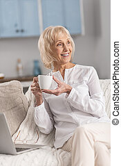 Dreamful mature woman distracting from laptop