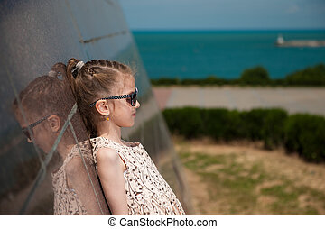 beautiful little girl in fashionable dress and sunglasses