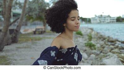 Dreaming black girl enjoying wind on shore - Side view of...