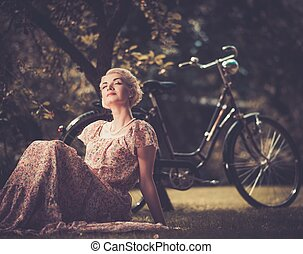 Dreaming blond retro woman in summer dress sitting on a meadow