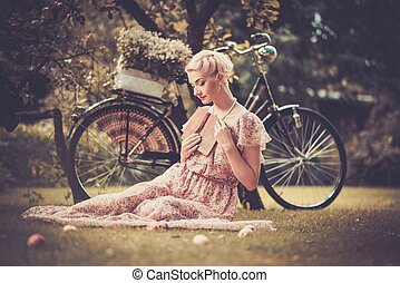 Dreaming blond retro woman with a book in summer dress...