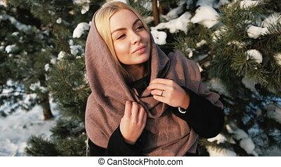 Dreaming blond woman looks far away in winter pine forest outside