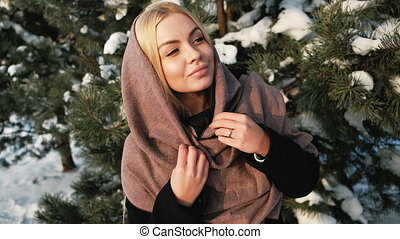 Dreaming blond woman looks far away in winter pine forest outside