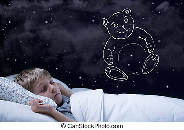 Image of little cute boy dreaming about his teddy bear