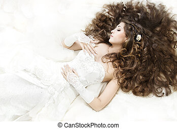 Dreaming bride with long curly hair lying down over white. Sleeping beauty. High angle view.