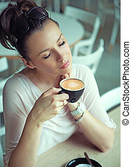Dreaming brunette lady with cup of coffee