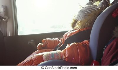 Dreaming cute child in a car in the child safety seat in...