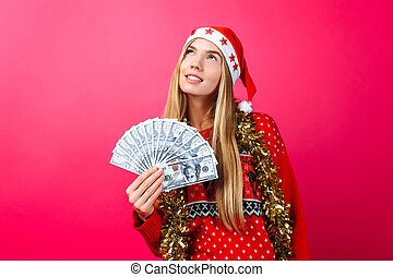 Dreaming girl in a red sweater and a hat of Santa Claus, makes plans and thinks where to spend money, keeps the money on a red background.