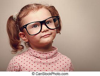 Dreaming happy kid girl in glasses. Closeup instagram effect portrait