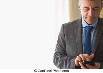 Dreaming man texting on his mobile phone - Dreaming mature...