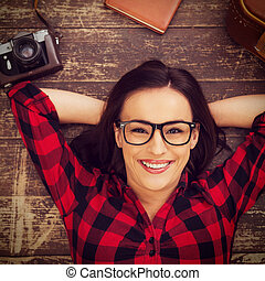 Dreaming of a big trip. Top view of beautiful young woman in eyewear lying on the hardwood floor and smiling while suitcase and camera laying near her