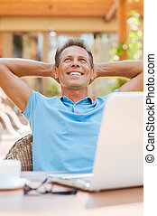 Dreaming of vacation. Relaxed mature man holding hands behind head and smiling while sitting at the table outdoors with laptop on it