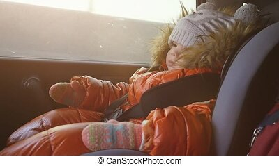Dreaming pretty child in a car in the child safety seat in slow motion on sunny day.