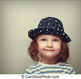 Dreaming smiling beautiful girl in hat looking up on empty space