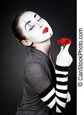 Dreaming woman mime with red flower on black background