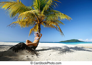 Dreaming woman sitting on the beach under a palm tree on a beautiful background of the sea.
