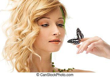 Dreaming young woman in conceptual spring costume with butterfly on her hand