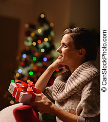 Dreaming young woman sitting chair with Christmas present box