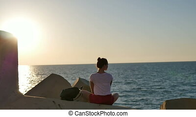 Dreaming young woman sitting on the rocks enjoying sea at sunset