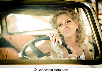 Dreamy bride drives in an old car