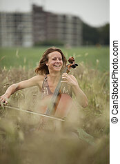 Dreamy celloplayer in nature