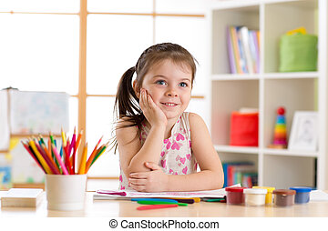 dreamy child girl with pencils in nursery