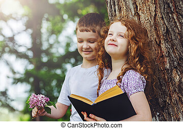 Little girl and boy reading book in the park.