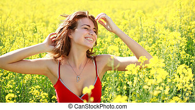 Dreamy girl enjoying the nature on a sunny day in the flowering yellow field