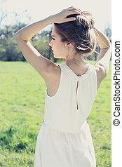 dreamy girl in a summer dress in a meadow