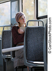 Dreamy girl in retro style clothes rides in a tram  on a summer day