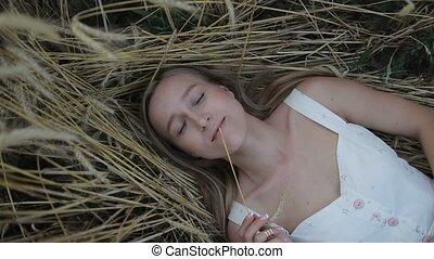 Dreamy girl lying on golden ripe wheat field