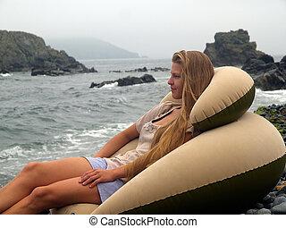 dreamy girl on the beach against stormy ocean