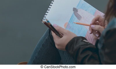 Dreamy girl painting a picture with pencils sitting at berth
