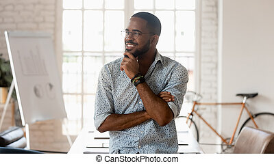 Dreamy happy african business man thinking of success in office
