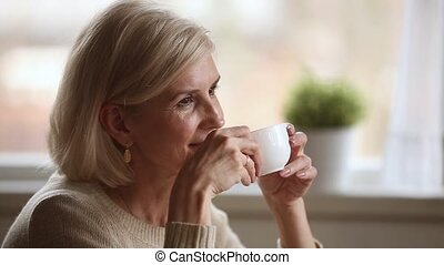 Dreamy happy middle aged woman looking away drinking morning...