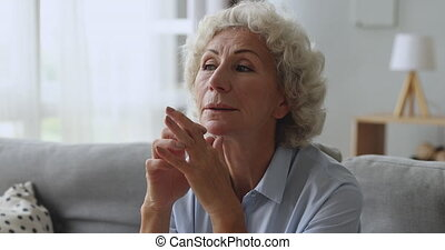 Dreamy mature middle aged woman thinking of good future.